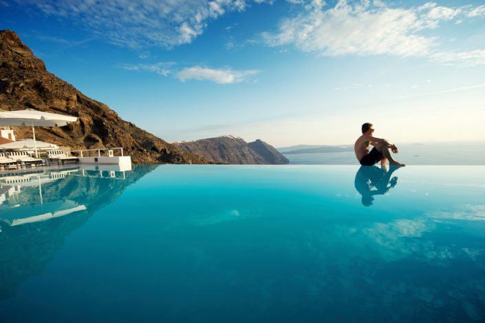 Man sits on edge of infinity pool looking out over view of Santorini caldera, Greece