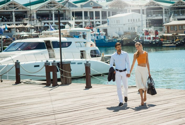 Wealthy young couple walking on dock away from yacht
